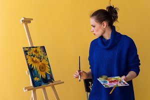 Girl artist paints sunflowers.