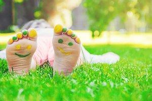 Child lying on green grass.