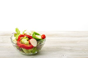 Full bowl of fresh salad on a white wooden table the background