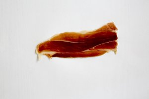 Isolated slice of jamon Serrano