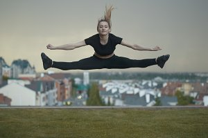Young caucasian girl performs twine jumping over background cityscape