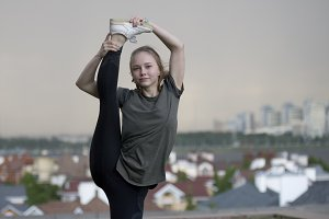 Young female acrobat standing on the leg in twine on background cityscape