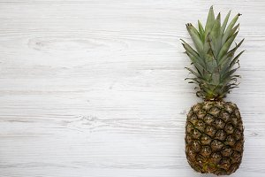 Ripe pineapple on a white wooden