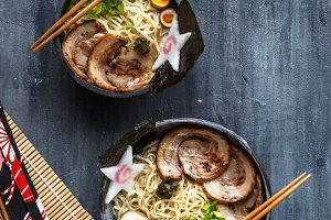 Two ramen bowls with pork, egg and chives, top view