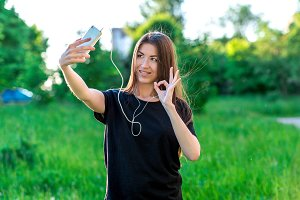Young brunette woman smiling happily in summer in park. Communicates in social networks. Hands gestures ok, I'm fine. I am fine. Emotional communication in a video call.