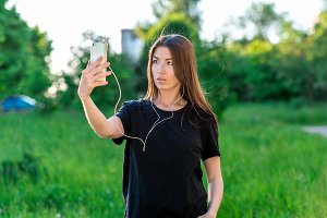 In summer, a girl in fresh air rests. Beautiful brunette European. Holds the hands of a smartphone. Watching video on the phone. Listening to music. Conducts a video broadcast by phone.