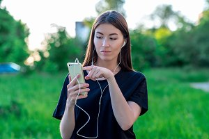 Girl in summer in a park nature. Holds a smartphone with headphones. Finger of the hand dials a message. Opens a new application. Listening to music rewinds a movie.