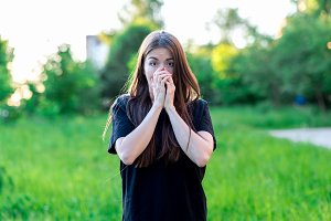 A brunette girl with long summer hair in nature in black T-shirt. Hands covering his mouth. Emotionally, fear is a surprise. Dressed in casual clothes. Large Surprised brown eyes.