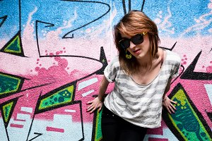 Stylish girl against graffiti wall