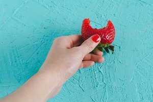 Hand holding a ripe strawberry on bl