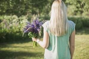 the girl is standing with bouquet