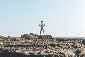 Man standing on the rocks in the ocean of Bali island. Indonesia.