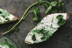 toast spread with cream cheese and basil, on grunge background