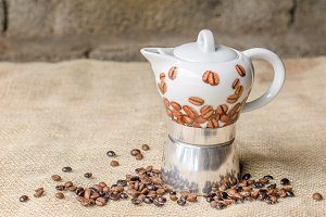 Coffee pot on rustic background.