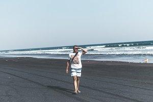 Man on the black sand beach. Bali island.