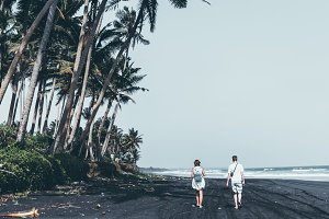 Couple on the black sand beach. Bali island.
