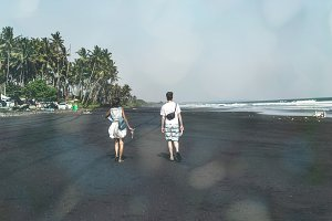 Couple on the black sand beach. Bali island.