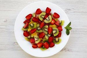 Fresh fruit salad on white wooden