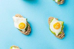 Healthy sandwich with fresh avocado and fried quail eggs