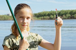 Happy teen girl preparing to fishing