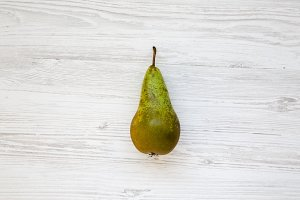 Ripe pear on white wooden background
