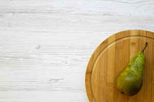 Ripe pear on a round bamboo board