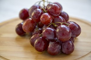 Bunch of ripe red grape on a round