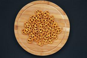 Salt pretzels on round wooden board
