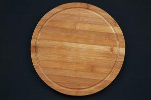 Round bamboo cutting board on a dark