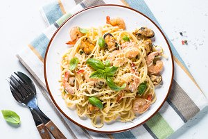 Pasta spaghetti with seafood and cream sauce on white.