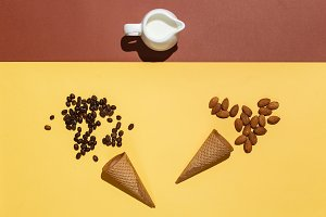 Concept of Preparation for ice cream or iced coffee. Cream jug, two waffle cups, scattered coffee beans and almonds on yellow brown table. Flat lay mockup