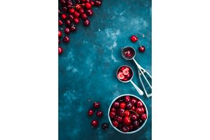 Cherries with an ice cream spoon and metal bucket on a grey concrete background, Summer berries concept with copy space. Neutral color tones still life
