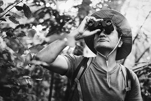 Man using binoculars in the forest