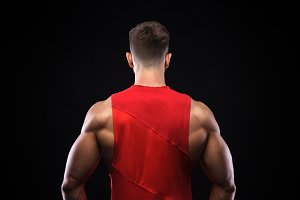 Back view of a muscular male model against black background