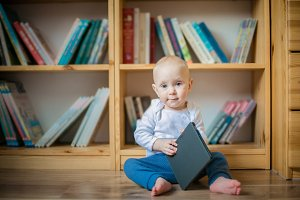 Toddler girl honding ebook in front of book shelves