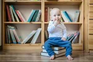 Toddler girl sitting with books in front of book shelves
