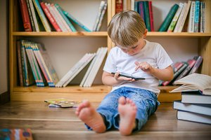 Boy playing with his smartphone in front of book shelves