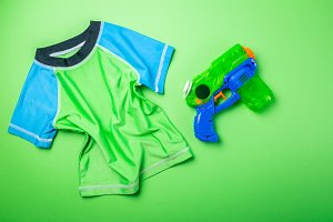 Summer fun concept - water gun and rash guard on bright background