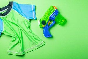 Summer fun concept - water gun and rash guard on bright background