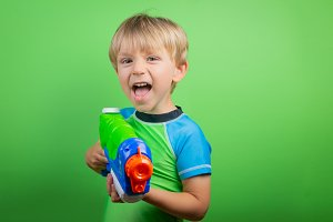 Boy holds water gun in front of bright green background