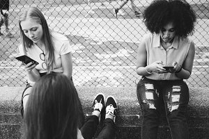 Friends using smartphones in a park