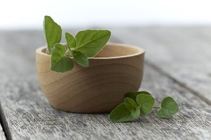 Herb Oregano in a bowl on rustic wooden background