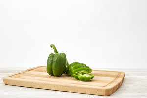 paprika green on wooden cutting board on white wooden