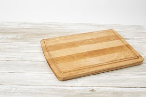 Empty bamboo cutting board on a white wooden table for product display