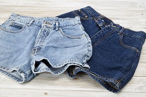 two vintage woman Jeans denim shorts on wooden shelf. shorts from new collection