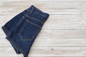 Woman's vintage denim shorts on wooden shelf
