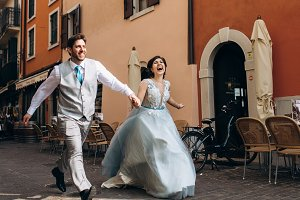 Laughing wedding couple runs