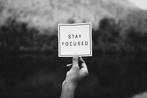 "Hand holding ""stay focused"" text"