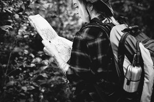 Woman checking map in the forest