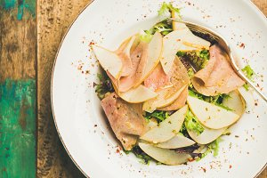 Fresh salad with smoked turkey ham and pear, rustic background
